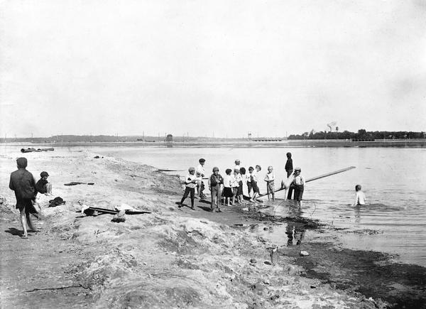 Group of children playing with a makeshift diving board at Brittingham Bay swimming hole.