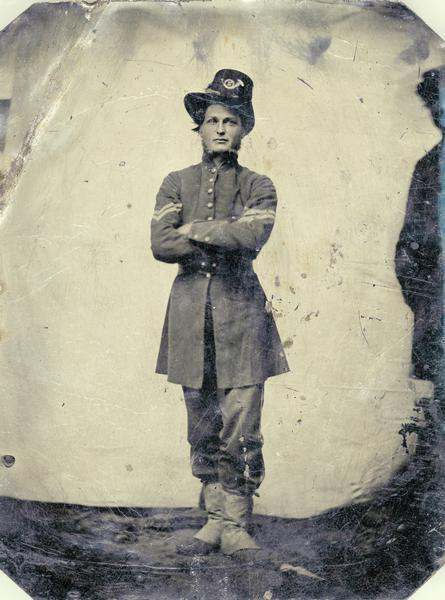 Ferrotype/tintype portrait of Corporal Cornelius Wheeler of Company I of the 2nd Wisconsin Regiment. Standing, facing forward with arms folded, in full uniform. This photograph was probably taken in the field shortly after the regiment received their distinctive Iron Brigade uniforms. On the first day at Gettysburg the Iron Brigade sustained its reputation as a fighting force, despite severe losses. The 2nd Wisconsin experienced a 77% casualty rate, and Wheeler, then a sergeant, ended the day as the most senior man in his company.