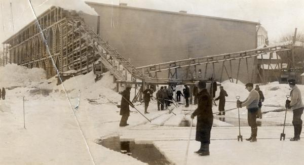 Men harvesting ice at the Conklin Ice House on Lake Mendota. The men are using pike poles to slide the blocks to the conveyor and U-shaped tools to split partially sawed blocks from ice. The steel frame of the new Wisconsin State Capitol is visible to the right of the icehouse.