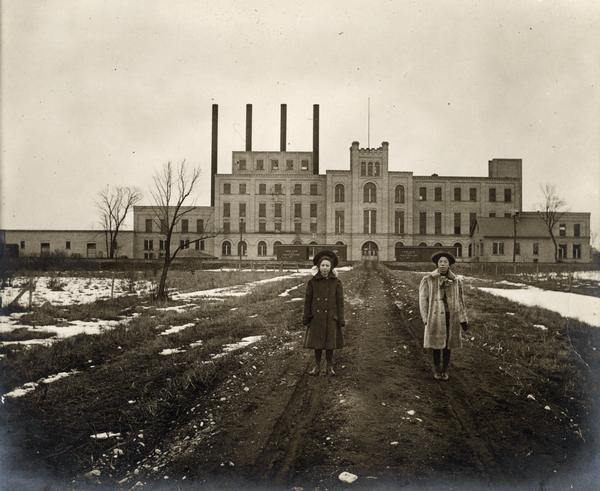 Two women standing on path in front of the Garver Feed Mill, which was originally a sugar beet processing factory.