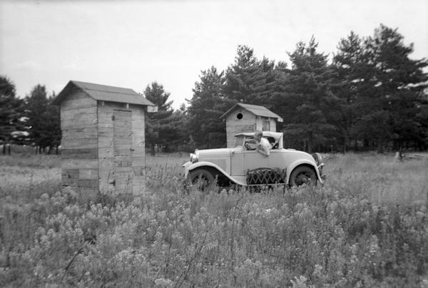 A man is driving an automobile in a field near two buildings, perhaps outhouses.