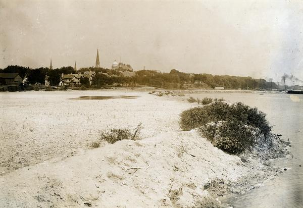 View of Madison from Lake Monona with the Wisconsin State Capitol building in the background. This view of Brittingham Park shows a part of the park shortly after if had been filled in by the sand dredge. The photograph was taken from the railroad trestle and looks north-easterly across the triangle-shaped part of the bay.