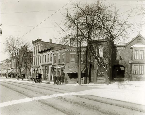 View of T. Gullman Shoes, Simon Brothers Vegetables, and H. J. Minch Flour, Feed, Grain and Hay on the north corner of the 400 block of State Street. There is a blanket of snow and men walking under the awnings of the store fronts.