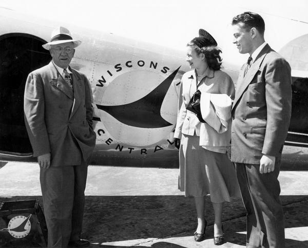 Margaret McGuire, the 1948 Alice in Dairyland, stands next to a Wisconsin Central Airlines airplane with Governor Oscar Rennebohm and another man.
