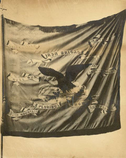 The flag of the Iron Brigade bearing the design of an eagle surrounded by the names of battles.