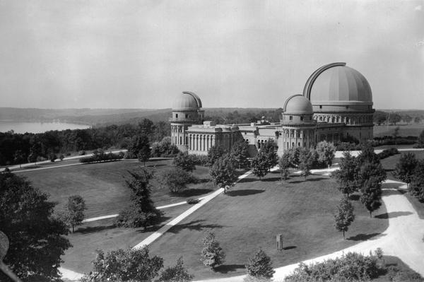 Elevated exterior view of Yerkes Observatory. Geneva Lake is in the background, left.  Roads and sidewalks cross the sweeping, well tended lawns.  The design of the grounds was based loosely on a plan by the firm of landscape architect Frederick Law Olmsted; the full plan was never implemented.  The grounds include several trees which are the largest of their species in Wisconsin and other interesting specimens.