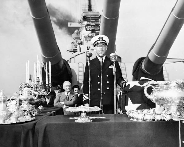 Captain Roper of the USS Wisconsin speaking aboard ship at a presentation ceremony of a silver service from the people of Wisconsin to the battleship. Governor Oscar Rennebohm is visible on the left.