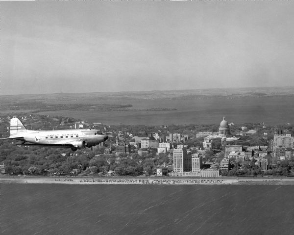 Aerial view of a North Central Airlines DC-3 airplane flying over the Madison isthmus. Clearly visible are the Wisconsin State Capitol, the 1 West Wilson Street State Office Building, and Lakes Monona and Mendota.