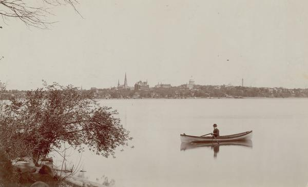 Man in a rowboat on Lake Monona with view of the city in the background.