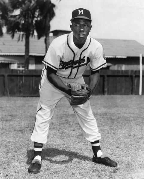 Henry Aaron poses in uniform on a baseball field.