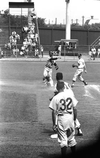 Milwaukee Braves shortstop Johnny Logan jumps over a sliding baserunner and throws to Braves' first baseman Frank Torre in a game at County Stadium.  Second baseman Red Schoendienst looks on from the right.  Schoendienst's first home game as a Brave after being acquired from the New York Giants was June 17, 1957.
