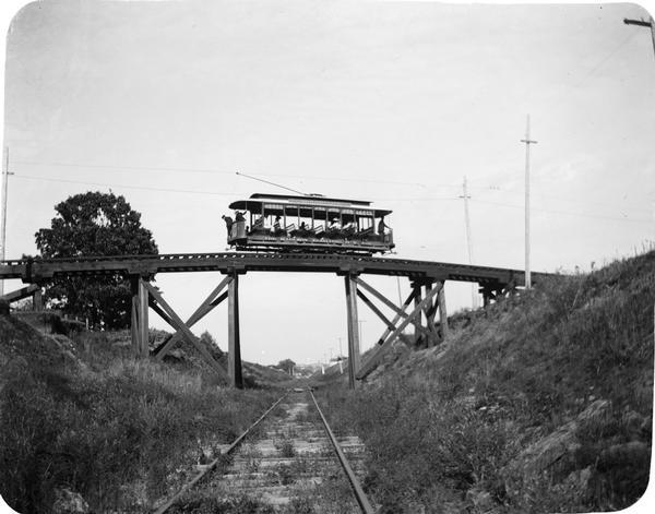 Rail car passing over the Harrison Street viaduct on the Wingra Park line. The line served the growing suburbs of University Heights, Oakland Heights, and Wingra Park. This car had ten bench seats running across the car and was rated as a fifty-passenger car. Such cars were extensively used for tranporting huge crowds back and forth to the circus grounds and for refreshing  summer rides.