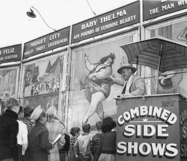 "State Fair barker announcing side show attractions to a crowd of children, featuring ""Midget City, the World's Tiniest Entertainers"" and ""Baby Thelma, 619 Pounds of Feminine Beauty."""