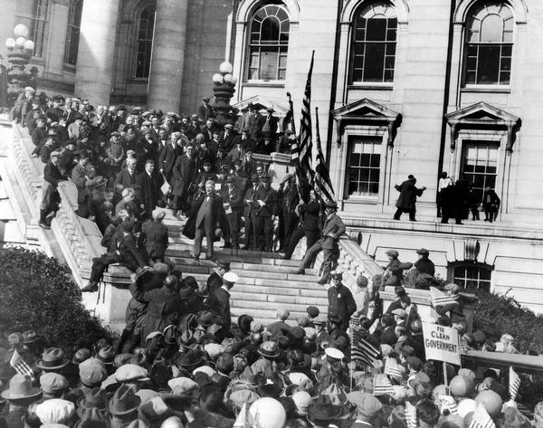 Robert M. La Follette, Sr. speaking to a large crowd from the Wisconsin State Capitol steps. This speech marked the end of his independent campaign for the presidency.  Photographers are perched on window sills and members of the crowd are waving flags and campaign signs.