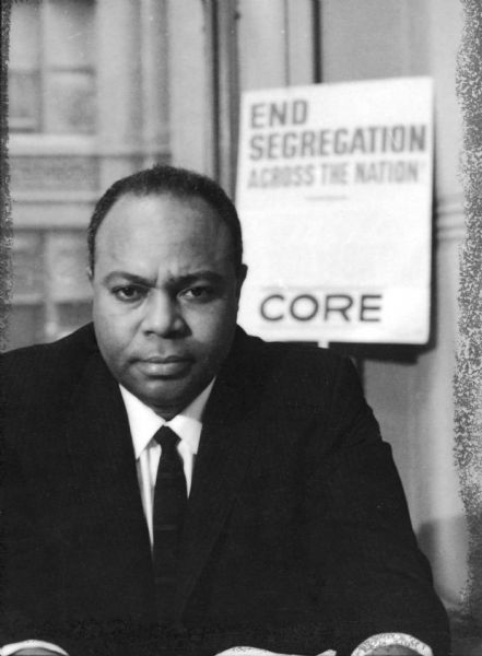 "Portrait of James L. Farmer, Jr. sitting at his desk with a ""End Segregation - CORE"" poster behind him. James Leonard Farmer, Jr. was a civil rights activist and leader of the American Civil Rights Movement. He co-founded the Committee of Racial Equality in 1942, which later became the Congress of Racial Equality (CORE). He was also the initiator and organizer of the 1961 Freedom Ride, which eventually led to the desegregation of inter-state transportation in the United States."