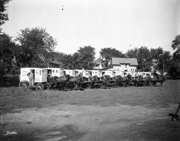 A line of Kennedy Dairy horse-drawn wagons with drivers posing beside them. For Quaker Oats Farm.