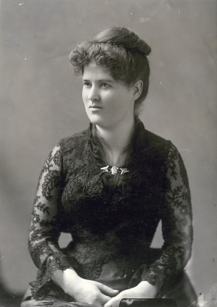 Formal studio portrait of Belle Case La Follette wearing a black lace dress. This photograph was taken about 1885, the year in which her husband, Robert M. La Follette, Sr., first went to Washington, D.C., as a Republican congressman.  It is probably a dress that she wore to official parties and gatherings in the capital.