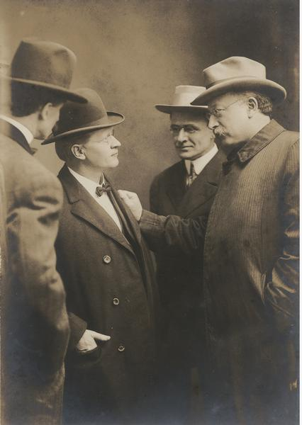 Group portrait of Emil Seidel talking with Fredrick C. Howe and Victor Berger, while another man stands off to the side.