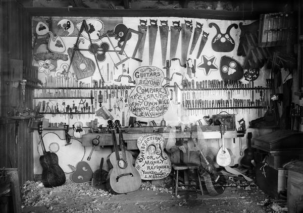 Interior of a guitar  maker's workshop, with a workbench, tools,  guitars, and other stringed instruments. In the foreground, there is a ghostly image of a seated man, likely that of the luthier, Leo Uhlmeyer. This effect was created by the photographer's use of a long exposure, and having Uhlmeyer leave the scene before the exposure was completed.