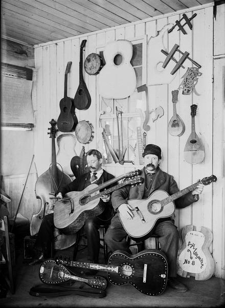 Two men are seated holding guitars in luthier Leo Uhlmeyer's store. There are more instruments on the floor in front of them and hanging on the wall behind them.