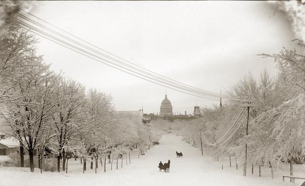 Winter scene looking down snow-covered Wisconsin Avenue to the third Wisconsin State Capitol. There are two horse-drawn sleighs, each with one passenger, on the street.