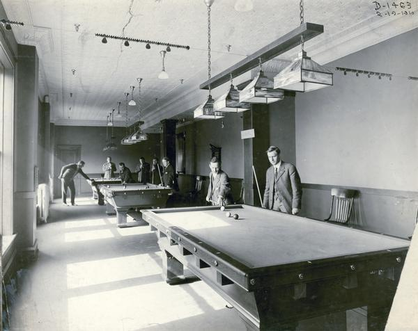 Eight gentlemen play billiards inside the Deering Works (factory) club house. The factory was originally built by William Deering for the Deering Harvester Company in 1880. In 1902 it became International Harvester's Deering Works. The factory was located at Fullerton and Clybourn Avenues and closed in 1933.