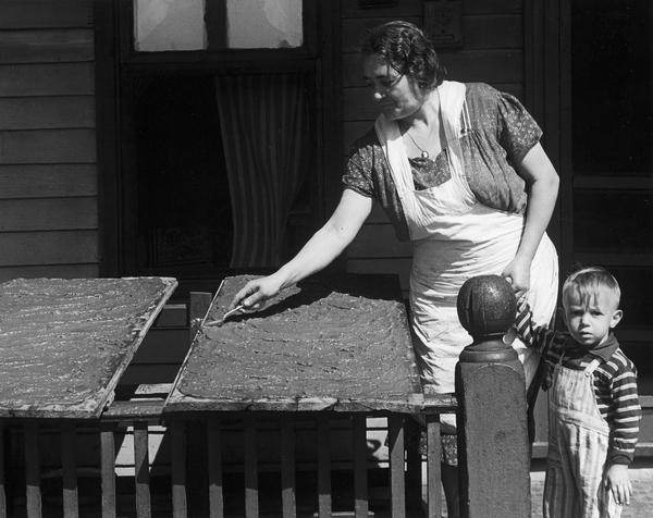 Loretta Falci (Lorenzina Fiocco Falci), an Italian woman, preparing sarsa, tomato paste on boards on the porch of her home, 622 Milton Street, as she holds the hand of a young boy (Joseph Anthony Pellittei). Milton Street is located in what was known as the Greenbush neighborhood.