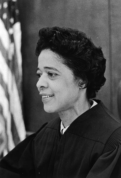Portrait of Vel Phillips in her judges's black robe with an American flag behind her. She was the 13th District Children's Court judge, the first woman and African American to hold this post.
