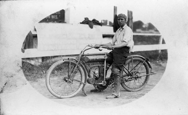 A young man sitting on a motorcycle.