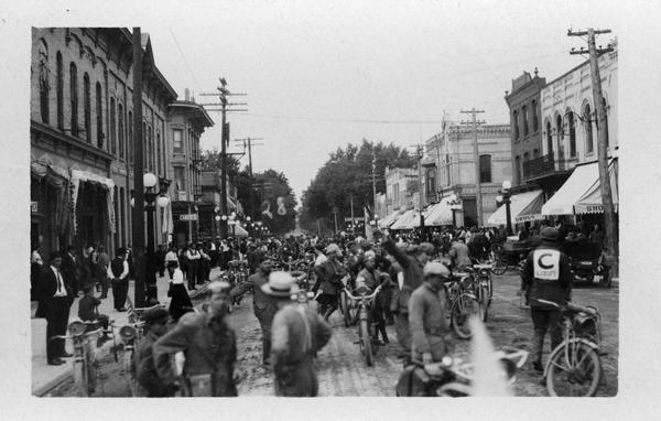 A crowd of people in the street, many of them with motorcycles, possibly getting ready to race.