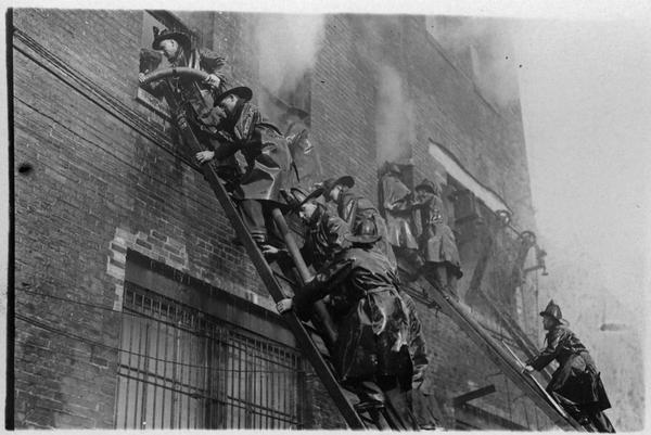Fire fighters on ladders climbing up to the windows of a burning building.