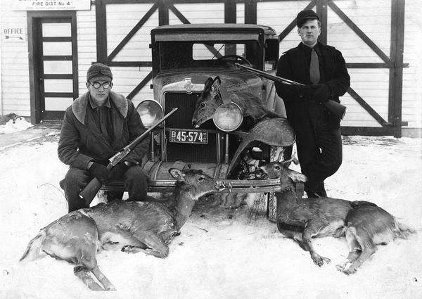 Two hunters with rifles pose in the snow by a car with three deer carcasses.