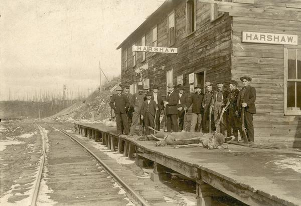 A group of men pose with guns and deer carcasses on the railroad platform at Harshaw.