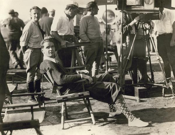 "Howard Hughes on the set of ""Sky Devils,"" a comedy about World War I aviation that starred Spencer Tracy. Hughes reused many of the airplanes he obtained for the 1930 production of ""Hell's Angels.""  Here he is on location superintending the shooting of the air scenes."