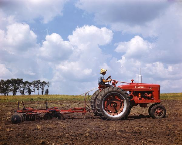 Color photograph of a farmer with a straw hat working a field using a Farmall M tractor with disc harrow against a bright blue sky strewn with fluffy white clouds. The photograph was most likely taken at or near International Harvester's experimental farm in Hinsdale, Illinois.