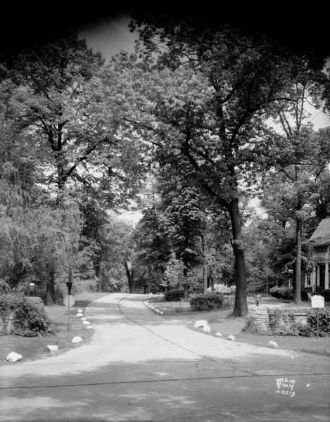 Rock lined Fuller Drive and the Adolph Jacob Taff house, located at 6 Fuller Drive. This is the western entrance to Fuller's Woods, in Maple Bluff.