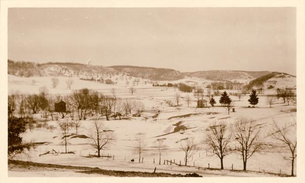 Two farmhouses and the surrounding snowy landscape near Taliesin, the home of Frank Lloyd Wright.