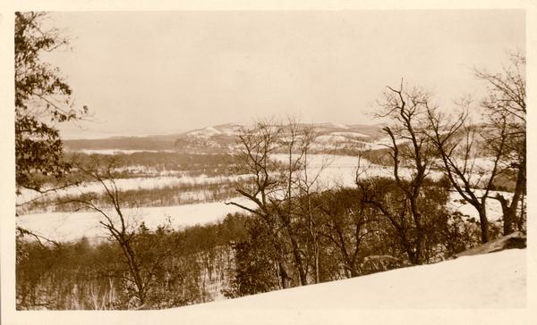 Winter scene of a snow-covered valley near Taliesin, the home of Frank Lloyd Wright.  The bridge over the Wisconsin River is in the distance. Taliesin is located in the vicinity of Spring Green, Wisconsin.