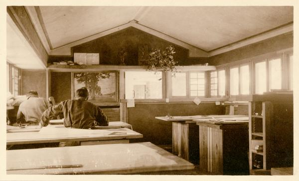 Draftsmen working at drafting tables in the workroom at Taliesin, the home of Frank Lloyd Wright. A painting by George Neidecken is on the left.  Taliesin is located in the vicinity of Spring Green, Wisconsin.