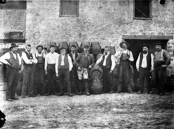 Brewery employees, many of them from the Schumacher family, posing with barrels outside the brewery.