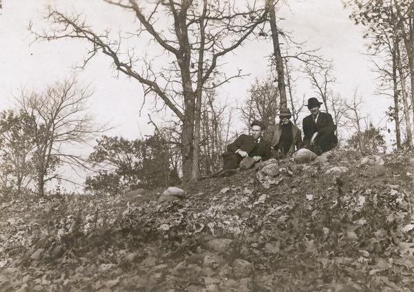 Reverend F.M. Gilmore, Professor W.E. Leonard, and Charles Brown relax on a burial mound on Fox Bluff near Lake Mendota.