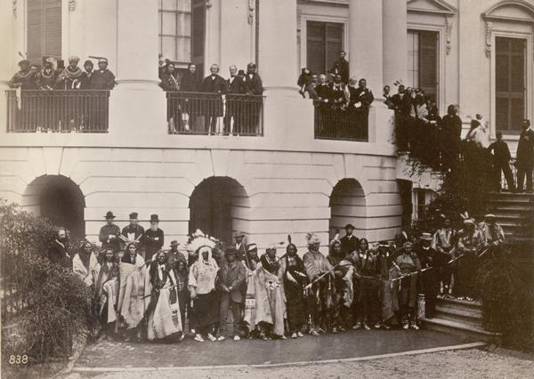 President Andrew Johnson and members of various Indian delegations and the White House staff pose outside the White House together.