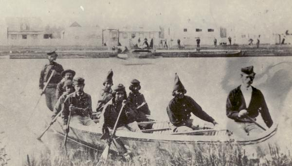 Nine men arrive at Fort William by canoe. Fort William, also called Kaministiguia, was the Hudson's Bay fur trading post.