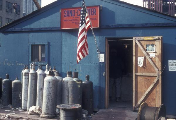 Office for the Sand Chapter of Mechanical Contractors at the construction site for the World Trade Center. The construction office has an American flag hanging by the front door and there are several acetelyne tanks to the left of the door.