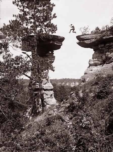 Ashley Bennett, son of photographer H.H. Bennett, is captured in mid-air as he jumps to Stand Rock.