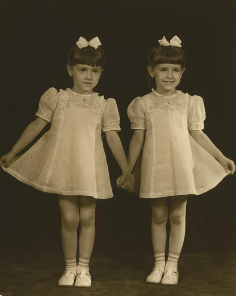 Dancing Kehl twins, Jo Ann and Jo Jean Kehl, born 1936. They wear matching dresses, shoes, and bows in their hair.