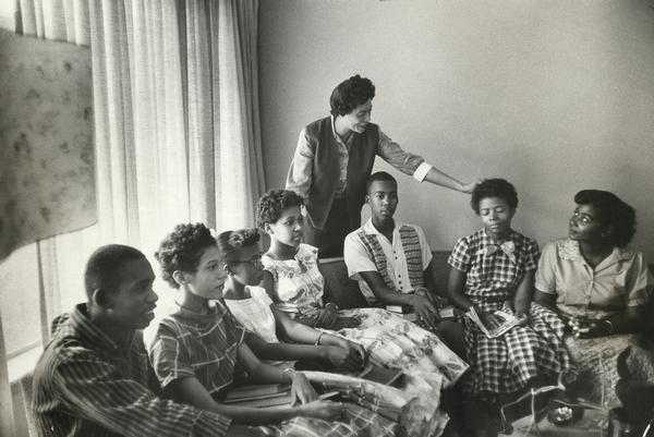 Daisy Bates, the head of the Arkansas NAACP, stands behind seven of the Little Rock Nine, who are seated on a sofa in her living room.  They have assembled there to await the arrival of the soldiers of the 101st Airborne Division who will escort them to school.  The students are Jefferson Thomas, Carlotta Walls, Thelma Mothershed, Gloria Ray, Terrence Roberts, Elizabeth Eckford, and Melba Pattillo.