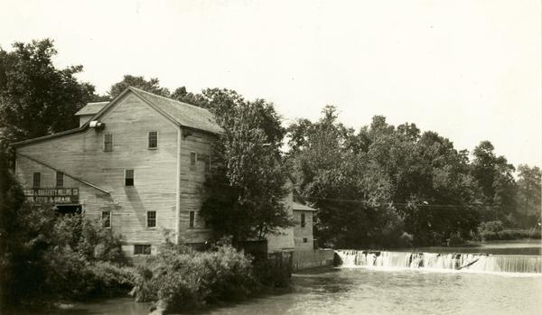 A large building, possibly a mill, next to a river.