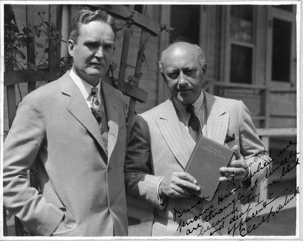 "Bruce Barton posing with Cecil B. Demille, who is holding a copy of Bartons' book ""The Man Nobody Knows""."