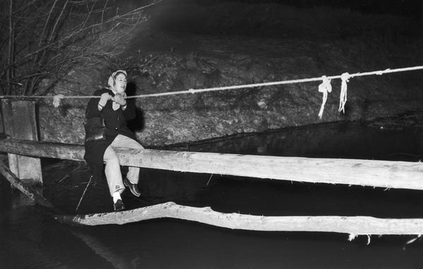 A woman in a headscarf crosses an improvised bridge in the vicinity of the village of Tamsweg, escaping from Hungary to Austria.